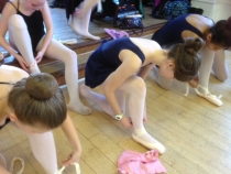 Some of the younger dancers are showing how to tie pointe shoes